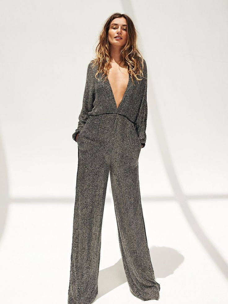 Mavis Jumpsuit | Inspired by decades past this wide leg sequin jumpsuit features allover sequin embellishments. Features a V-neckline with an open slit detail in back, the top is semi-sheer with dolman style long sleeves. Pants are lined with hip pockets.