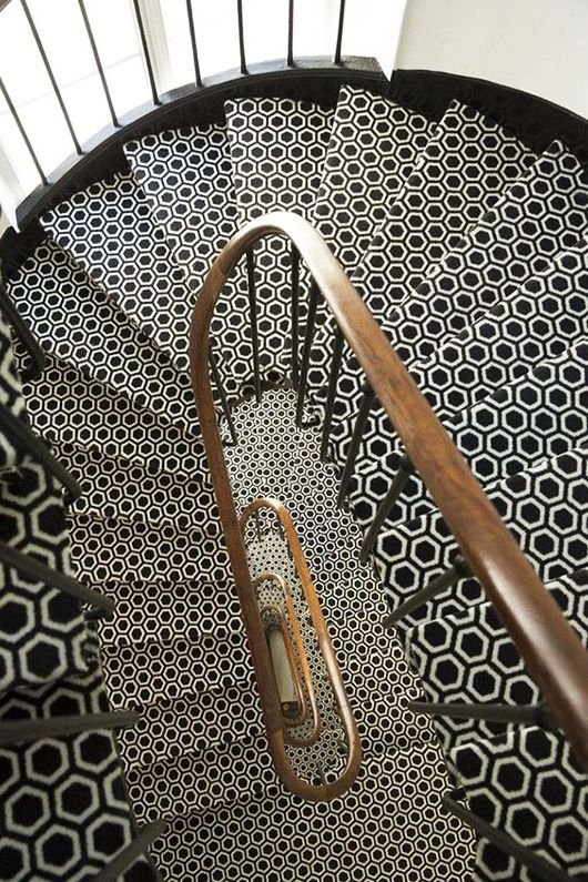 black and white hexagon tile staircase with wood railing.