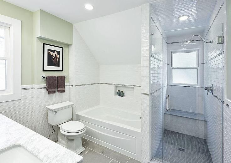 Lovely bathroom features a nook with sloped ceiling filled with a  drop-in tub and a white tiled surround accented with gray mosaic border tiles.
