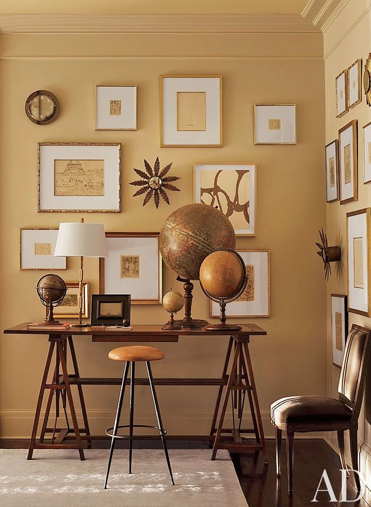 Prints and drawings by Pablo Picasso, Carolyn Carr, and others fill a wall in the family room of Suzanne Kasler's Atlanta home; a drafting table holds a collection of antique globes.
