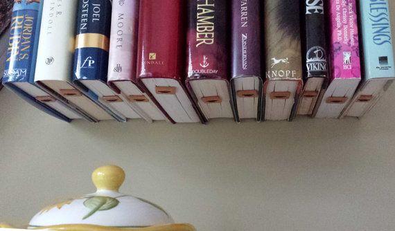 Biblioteca de pared de tus libros favoritos. ¿Quieres una manera única de mostrar y almacenar tus libros? Esto es él. El cordón es de cuero auténtico indio y se usa junto con un botón de madera para sostener el libro sin dañarla, solo pequeño cable poco marcas. Pesca de línea puede sustituirse por cuero pero es hecho a la orden a estado con su orden. Este carril es 2.2 x.75 x 28. viene con 12 colgadores de libro, puede ordenar suspensiones adicionales en $13. También puede pedir un menor o…