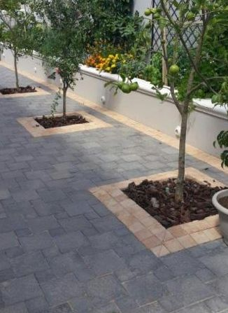 Landscaping product: Combination of Promenade 220x220x50 mm/110x110x50 mm cobbles in Charcoal with a Desert Sand 110x110x50 mm cobble border.