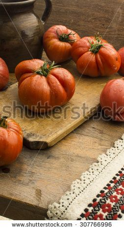 Freshly pick tomatoes, place on wooden chopping board and table