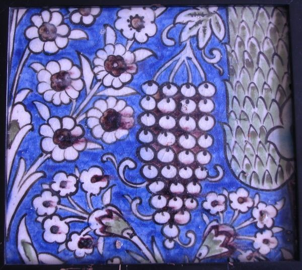 Heavy pottery tile, Damascus, early 17th century decorated in polychrome composition depicting a cypress tree with grapes and flowers on blue ground h 26 cm, w 23 cm, framed