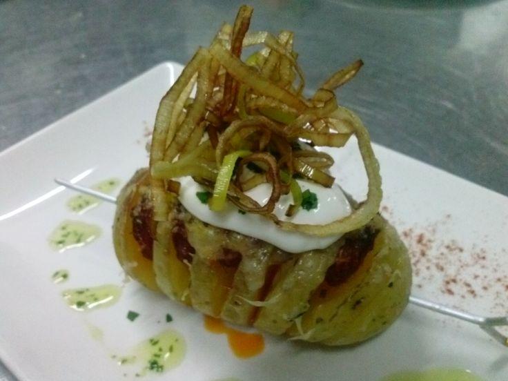 Patata asada rellena con chorizo y provolone cubierta con crema de queso y crujiente de puerro.