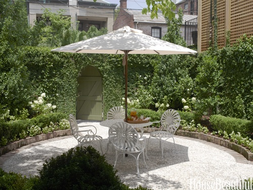 Tucked into the backyard, the walled courtyard garden is a fragrant oasis lush with jasmine, hydrangeas, orange trees, and creeping fig. Antique bricks and boxwood define the form, and crushed oyster shells cover the ground. The 1950s iron table and antique French garden chairs are shaded by a Pottery Barn umbrella. Garden design by Marshall Stone.