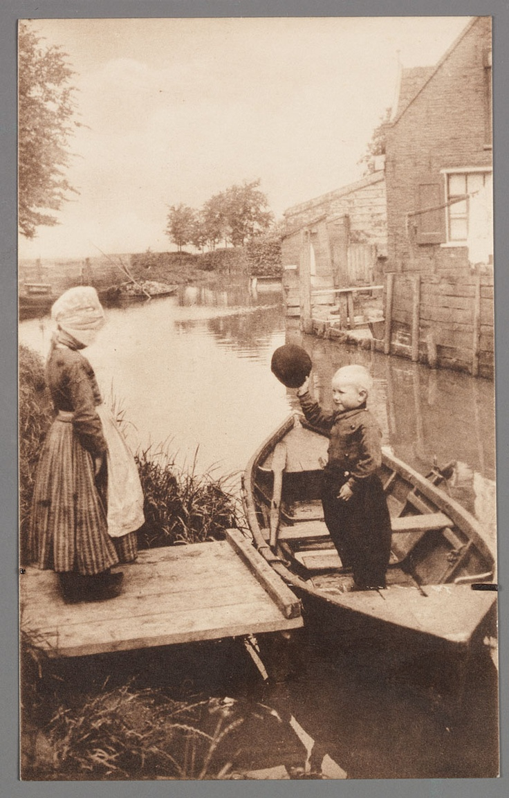 Goeden dag Grietje. Good day, Grietje. Meisje in dracht staat op het steigertje. Jongen staat in de roeiboot en neemt zijn hoed af. 1905-1920 #NoordHolland #Volendam