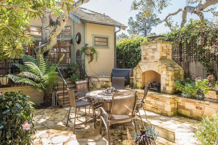 Mediterranean Backyard With Flagstone Patio and Outdoor Fireplace This Mediterranean-style backyard features a flagstone patio, outdoor fireplace, lush foliage and tabletop fire pit.