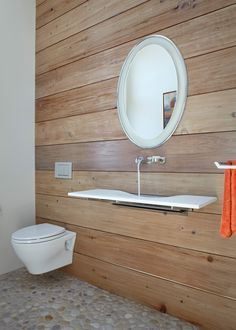"""Here's a lovely and minimalist small bathroom, featuring a wall-hung toilet and sink, and wall-mounted faucet. It looks so more spacious than it is. I love the pebble stone floor, too. Only problem is you would have to live the clutterless life of a monk: where do you store the soap, and other essentials?  """"Wall-mounted toilets are ideal for small bathrooms because they occupy zero floor space and they make the room look more spacious overall."""""""