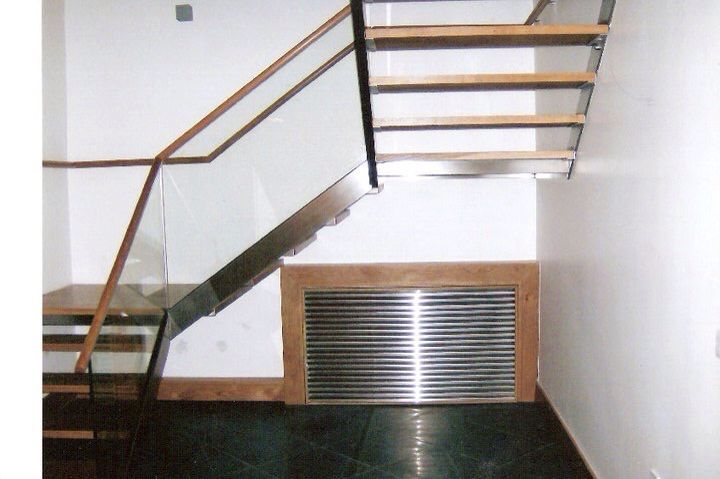 Stainless steel staircase with oak handrail, and stainless steel louvred cover for radiator or heat pump