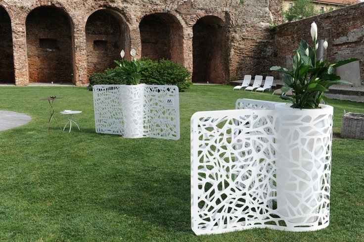 Struttura copri-vaso separè in varie misure e tipologie realizzato in lamiera accoppiata traforata verniciata in bianco. Disponibile in versioni personalizzate con marchi e colori a richiesta.    Outdoor planter-covers which function as partitions in various sizes and types made of perforated sheet metal bonded white paint. Available in custom colors and brands on request