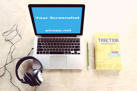 MacBook laptop next to the Traction book and headphones. Perfect image for marketing and promo apps.  Customize this image with your own app on PicApp.net - easy & free.  #Macbook #traction #desk