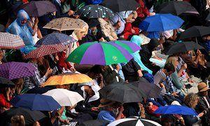 Umbrellas go up as rain stops play on Wimbledon's centre court.