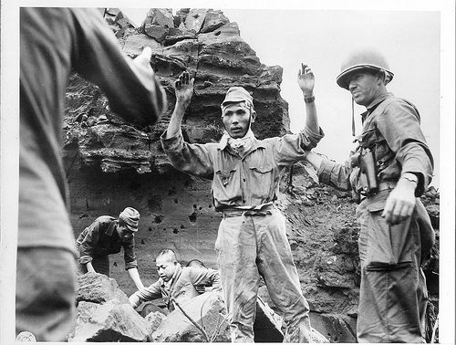 """Japanese Surrender on Iwo Jima First to emerge from an Iwo Jima cave in which, with twenty other Japs they had been hiding for several days, these Japs are astonished to find they are treated kindly instead of being tortured, as they were led to believe would be their fate if captured. (That's the photo caption as i found it)"""