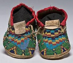 native american, America, Arapaho child's beaded buffalo hide moccasins, sinew-sewn and designed using red white-heart, light and dark blue, pea green, and greasy yellow seed beads; red cuff.