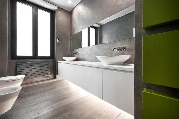 baño con lavabos sobre mueble blanco, sanitarios de pared, paredes de microcemento, suelo parquet