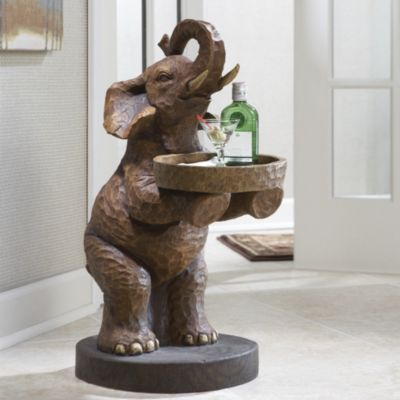 """Elephant Butler Table $139.00 $20.00 per month Ginnys Elephants have been photographed in the wild standing on hind feet to reach a high tree branch to munch on leaves. This pachyderm, however, rises to offer you a snack on its oval tray, hold a drink for a guest, or provide a spot to keep your keys. Crafted of resin to mimic hand-carved wood, it makes a unique accent table that's sure to be the talk of all who see it. Resin. 13"""" w x 27"""" h x 17 1/2"""" d."""