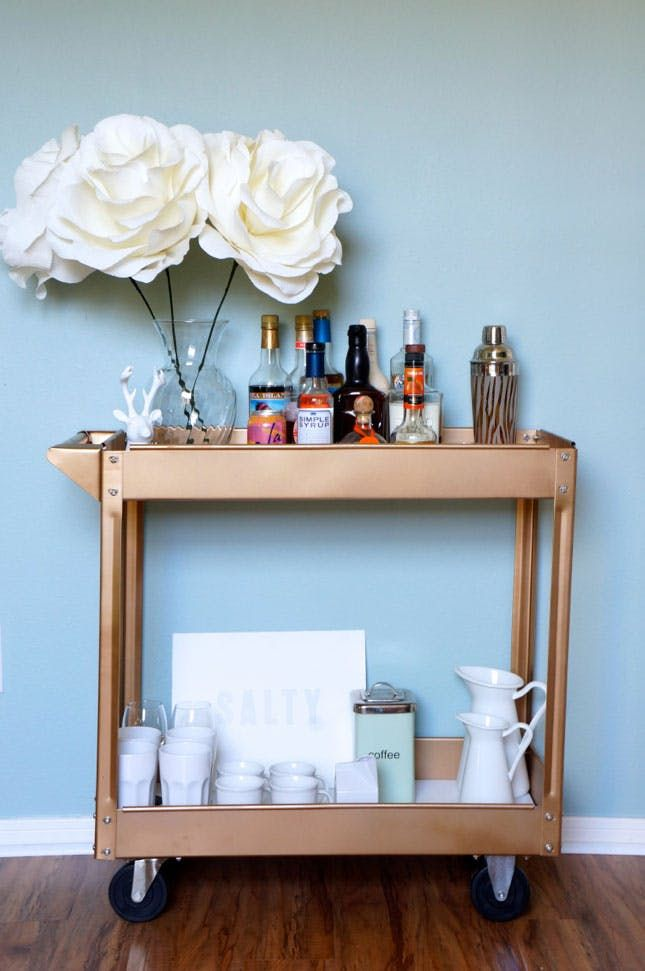It seems like no modern house or apartment is complete without a hip bar cart (where else will you showcase your dashing decanters?). Since they can get pretty pricey, we were thrilled when we learned of an easy way to turn a $40 tool cart into a luxe bar cart. We decided to put our own Lover.ly spin on it and take it from industrial and masculine to all-out glam. While the shiny red cart is cute as-is, (you definitely don't need to paint it), we wanted to give it some polish with a few c...
