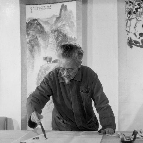 Shi Lu paints a lotus flower, 1981. Image courtesy of Shi Lu's family.