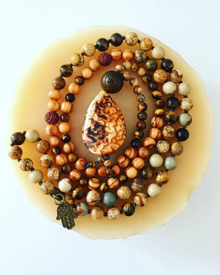 """A powerful protection Mala that brings strength, courage and positivity to the wearer. Relieves anxiety, fear and tension in those who are prone to stress. Also a symbol of good luck and longevity.  108 bead Mala with Olive Wood, Tiger Eye, Picture Jasper and Lava Rock beads. A bronze Hamsa protection charm on the back and an Agate teardrop focal stone. ~Aromatherapy Compatible~ Hangs at about 20"""""""