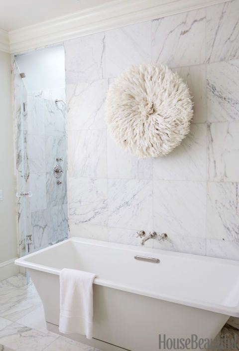 Calacatta marble walls and a gleaming Rêve tub by Kohler brighten the master bath. All fittings are by Harrington Brass Works. The wall hanging is by L'Aviva Home.Click through for more designer bathrooms and the best bathroom decor.
