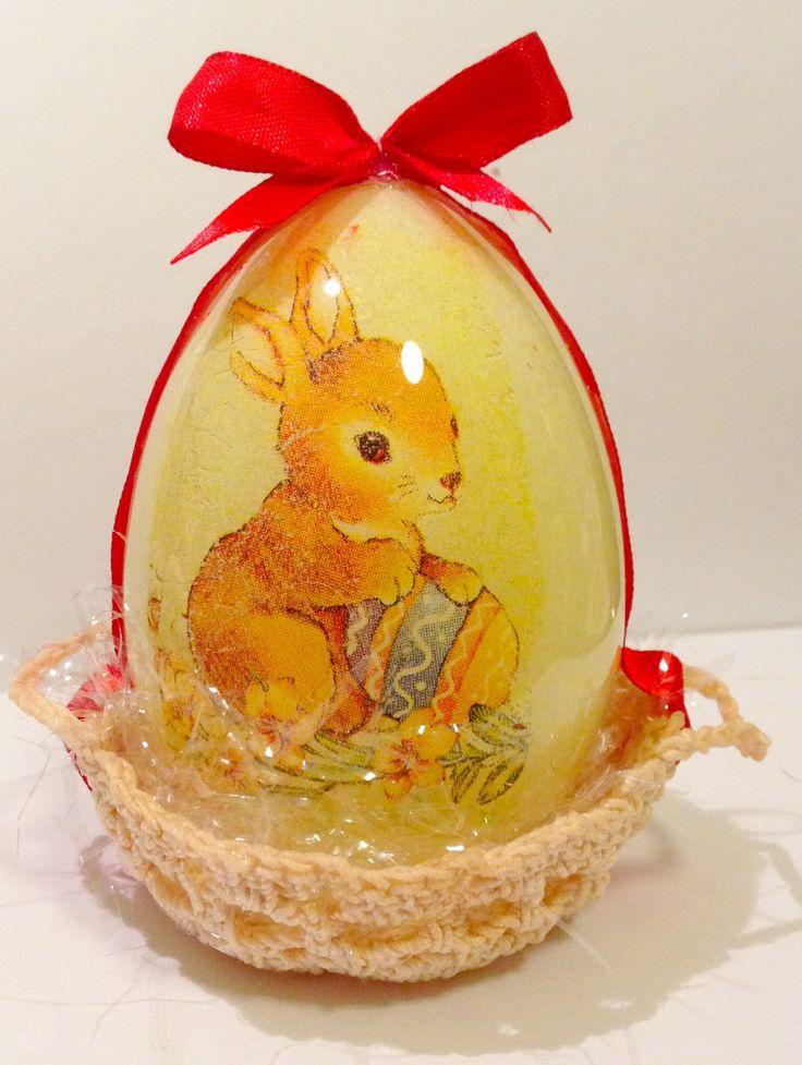 Uovo di Pasqua in plexiglas alto 11 cm decorato a mano e disposto su un letto di paglia dentro un cestino lavorato all'uncinetto.