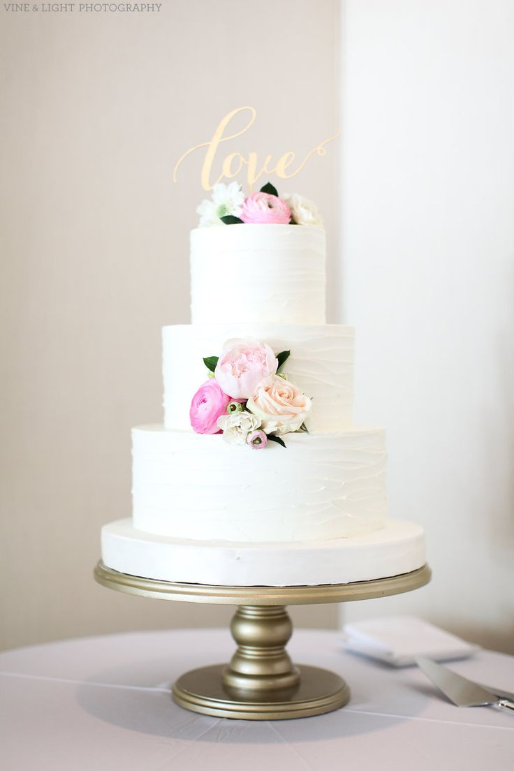 a simple and elegant wedding cake is dressed with light pink and white ranunculus, white scabiosa, blush peony, blush roses and white spray roses.