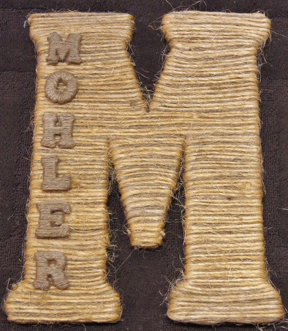 large rustic wall letter wrapped in hay twine and personalized with small letters displayed spelling out