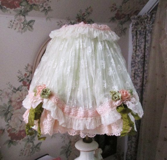 heres a cutie    started with almost new small sturdy spider style shade...    then added the prettiness...    made of palest minty green satin with palest minty green lace...oooo la la  trimmed out with salmon pink laces and pink and green roses and ribbons and bows...    its adorable, and so so darling cottage....    small to slightly medium in size    10 long and wide at bottom  4 across top