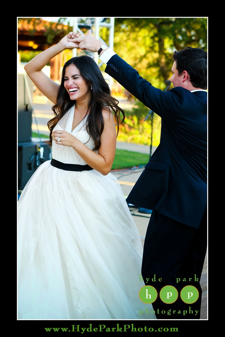 The bride and groom share a first dance in this outdoor natural setting. The bride even had a chance to change her sash to a black one for the after party! Photo by Austin Wedding Photographers, Hyde Park Photography. Venue is the UT (University of Texas) Golf Club. http://www.HydeParkPhoto.com