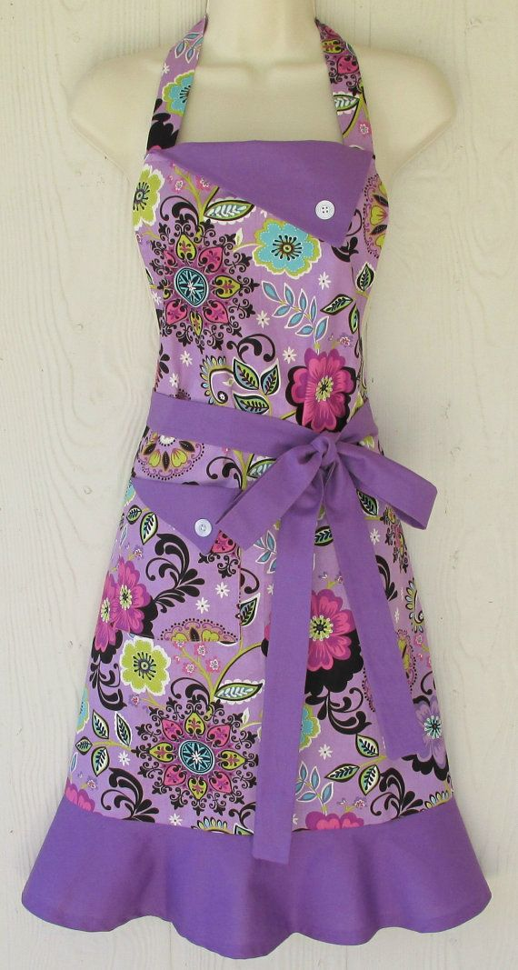 This retro style full apron is a floral print predominately in orchid. A darker shade of orchid is the perfect accent fabric for this vintage inspired apron.    Ties are extra long to fit and flatter many body types and sizes. A sturdy, lined pocket in the front makes this apron perfectly practical for daily use.    Electasie is all about quality - beautiful and durable fabrics, meticulous attention to detail (like adorable buttons and bows), and finished serged edges for a clean and…