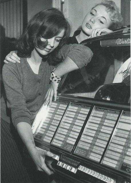 Listening to music on a Wurlitzer 1800 jukebox, mid 1950's