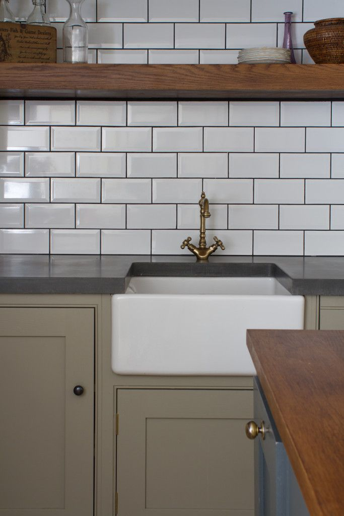 A traditional Belfast farmhouse sink with an in-keeping Tre Mercati French Classic tap. White metro tiles with dark grouting add contrast to the polished concrete worktops. Oak shaker cabinets painted in Paper & Paints Egyptian Grey. The ammonia stained oak island worktop and shelf are also visible.