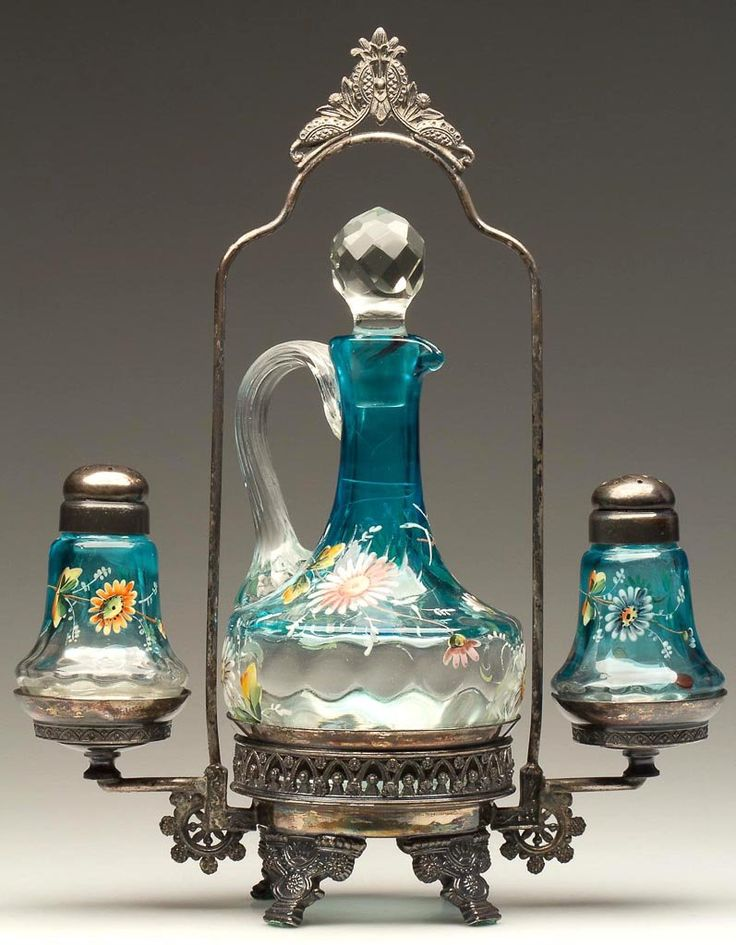 "THUMBPRINT - FLARED BASE THREE-PIECE CONDIMENT SET, turquoise shaded to colorless with polychrome floral decoration, comprising a salt and pepper shaker with matching period two-part lids, and a cruet with facet-cut stopper. Fitted in a quadruple-plate stand appears to be marked ""AURORA / S.P.MFG. / CO."" Fourth quarter 19th century"