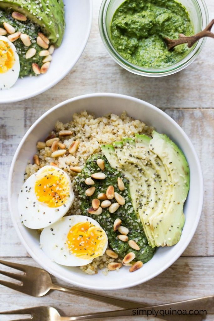 Savory Pesto Quinoa Breakfast Bowls topped with a soft boiled egg, sliced avocad…