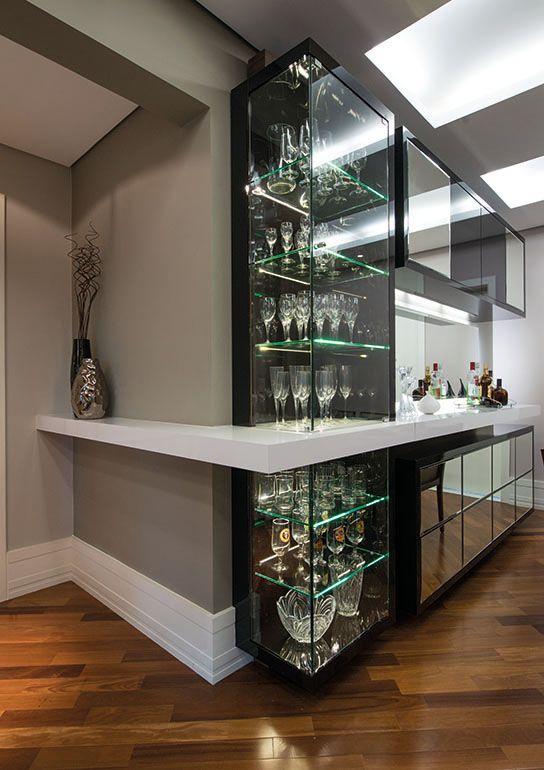 """Ao lado do espaço de jantar, foi projetada uma cristaleira que é """"cortada"""" pela estrutura que se estende do bar à parede perpendicular, formando um L."""