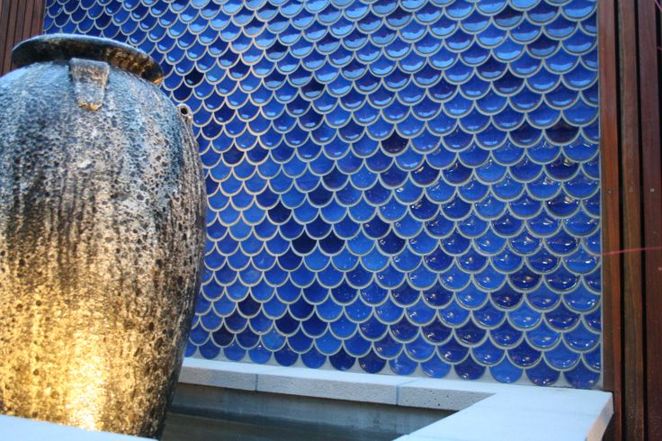 Lovely blue fish scale tiles provide the perfect backdrop for a water feature by the sea.Design by RPGD. www.rpgardendesign.com.au