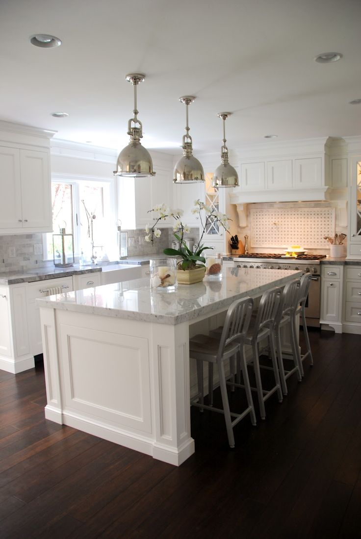DARK WOOD FLOORS The Granite Gurus: The perimeter countertops are Super  White quartzite with a Mitered edge detail. The island countertop is  polished ...