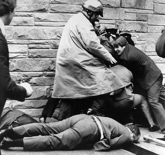 White House press secretary James Brady lies wounded on the sidewalk outside a Washington hotel after being shot during an assassination attempt on U.S. President Ronald Reagan, Monday, March 30, 1981. In the background secret service agents and police wrestle the alleged assailant to the ground.