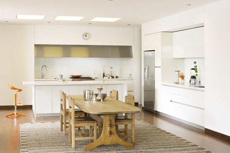 eN ESTA VISTA GENERAL se aprecia lo cómoda que es la cocina y el contraste entre la madera de los muebles y el blanco de todo lo demás. A la derecha, licores de The Wine Store y tabla de madera de Cahivaches