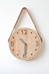 wooden clock that hangs with string to be held up