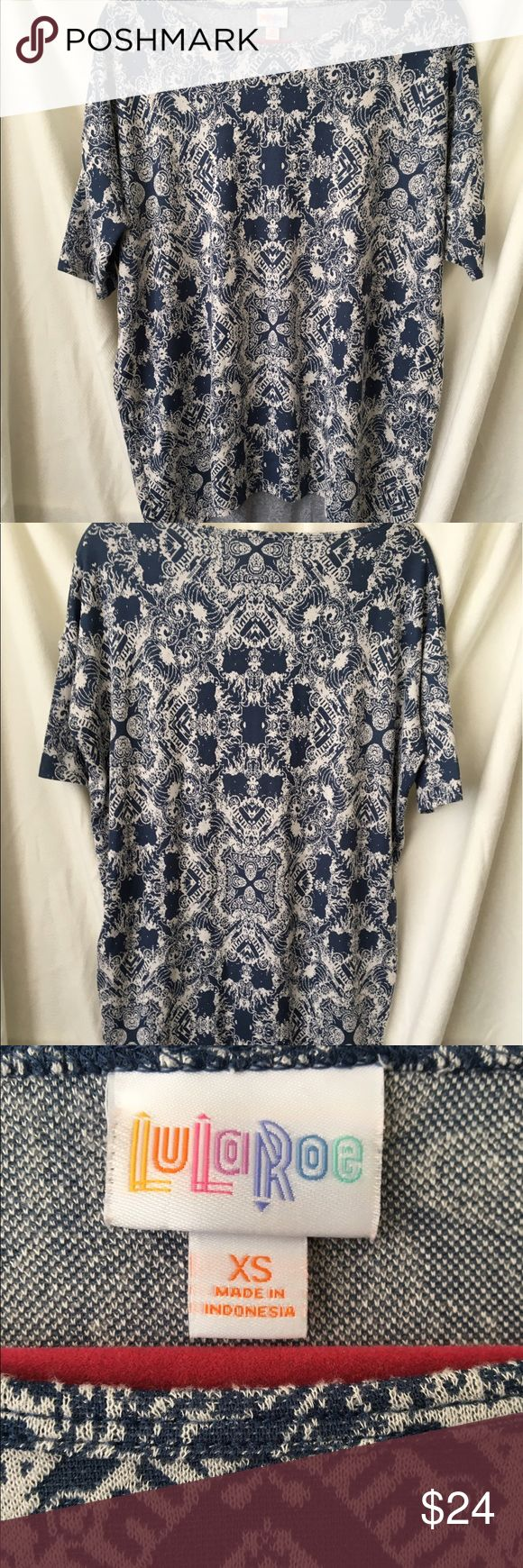 """Lularoe Irma top blue white short sleeve XS Lularoe Irma top size XS, high in front, lower back, short sleeve, blue and white filigree type print. Great condition! Slight dolmain type sleeves. Measurements: armpit to armpit 24.5"""", length 33"""" LuLaRoe Tops Tees - Short Sleeve"""