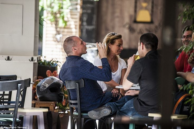 Down the hatches: Outgoing Greek finance minister Yanis Varoufakis drinks a beer in a bar ...