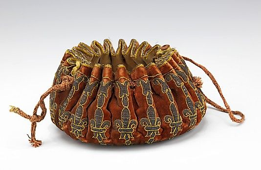 "Gaming purse, French, late 17th C. Made of silk, leather, metal.  like ""Put"" or ""La Bête."" Made of velvet or brocade, the bags are often heavily embroidered with silver and gold metallic threads. This example has a band of embroidered fleur-de-lis motifs, an indication of a French origin. Like others of the type, it has a round flat bottom and closes by means of a drawstring at the top edge."