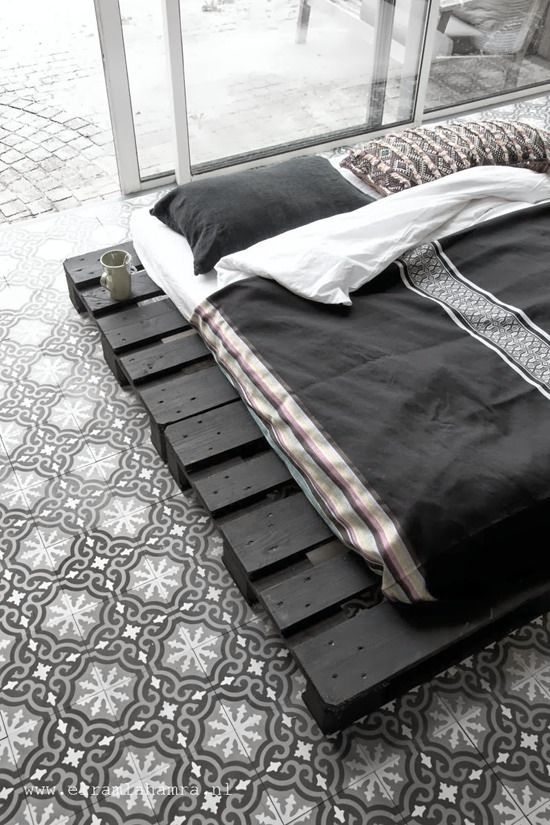 Zum schwarz-weißen Farbkonzeot des Schlafzimmers passt der Fliesenboden perfekt
