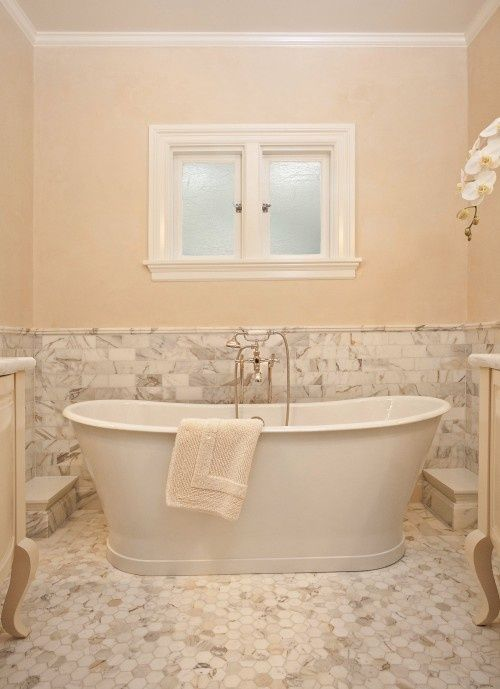 Calacatta Gold tile -- hexagon mosaic on the floor, and a solid slab under tub with the mosaic trim around to define it. will show you
