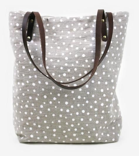 This large screen-print linen tote bag with brown leather handles features a polka-dot design, which never goes out of style.