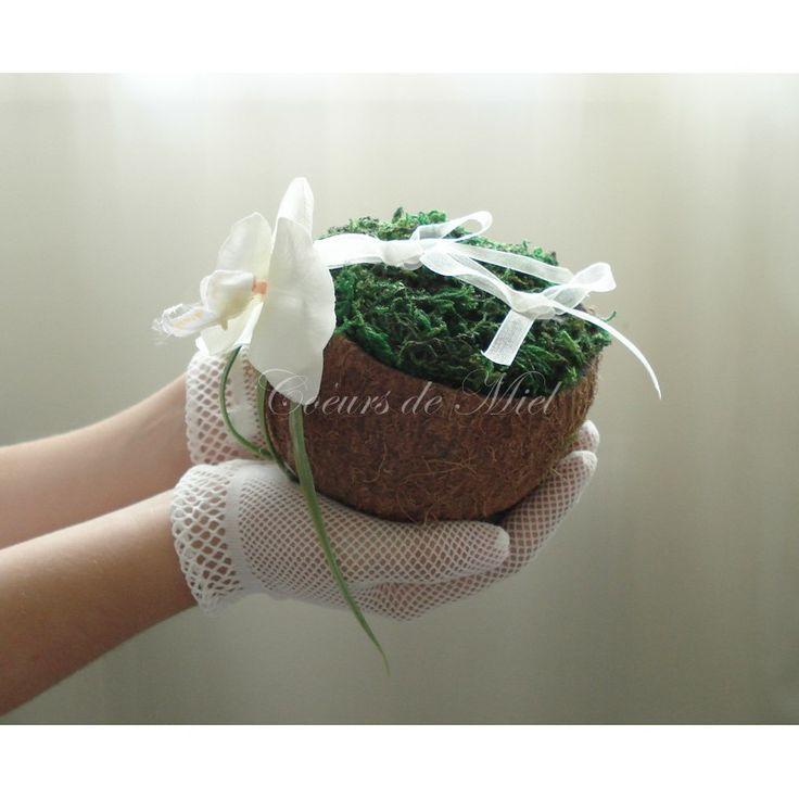 Simple et nature, ce porte alliance sera idéal pour un mariage au thème exotique. Réalisé à partir d'une noix de coco, ce coussin d'alliance est orné d'un fleuron d'orchidée et de mousse végétale. Vous pourrez y maintenir vos alliances grâce aux rubans d'organza.