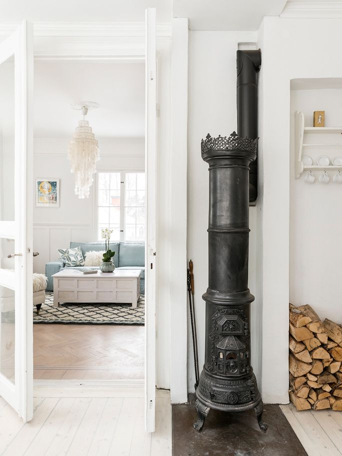 Traditioneel houten huis in Zweden met wit Scandinavisch interieur en originele houtkachel. // via The Style Files