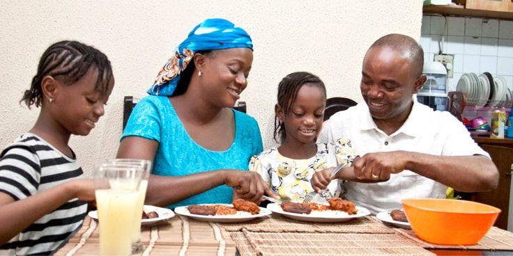 Un mari et sa femme mangent avec leurs deux filles dans une ambiance joyeuse